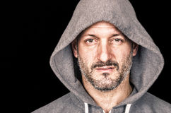Serious anrgy man with hooded sweatshirt. Looking at the camera stock photo