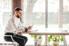 Serious applicant sitting in boardroom, preparing for interview with employer. Serious applicant sitting by desk in boardroom and waiting for employer questions royalty free stock images