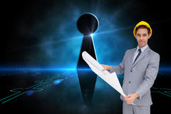 Serious architect with hard hat holding plans. Composite image of serious architect with hard hat holding plans Royalty Free Stock Photo