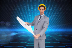 Serious architect with hard hat holding plans. Composite image of serious architect with hard hat holding plans Royalty Free Stock Photos