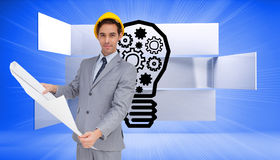 Serious architect with hard hat holding plans. Composite image of serious architect with hard hat holding plans Stock Photography