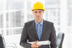 Serious architect holding blueprints looking at camera Royalty Free Stock Photography