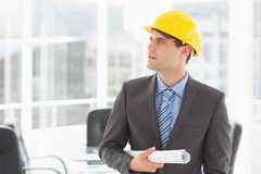 Serious architect holding blueprints looking up Royalty Free Stock Photography