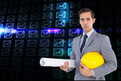 Serious architect holding plans and hard hat. Composite image of serious architect holding plans and hard hat Royalty Free Stock Photo