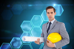 Serious architect holding plans and hard hat. Composite image of serious architect holding plans and hard hat Stock Photos