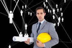 Serious architect holding plans and hard hat. Composite image of serious architect holding plans and hard hat Royalty Free Stock Image