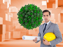 Serious architect holding plans and hard hat. Composite image of serious architect holding plans and hard hat Stock Image
