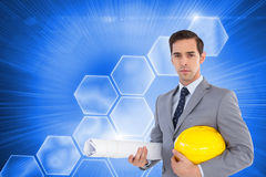 Serious architect holding plans and hard hat. Composite image of serious architect holding plans and hard hat Stock Photography