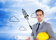 Serious architect holding plans and hard hat. Composite image of serious architect holding plans and hard hat Royalty Free Stock Photos