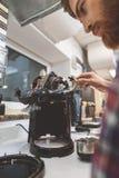 Serious artisan renovating coffee machine Stock Photos