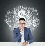Serious Asian businessman at a table, dollar cloud. Portrait of a young Asian businessman wearing glasses and a blue suit and sitting at a table. Blackboard royalty free stock image