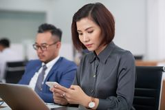 Businesswoman using mobile phone during meeting. Serious Asian businesswoman sitting in front of laptop computer and using her mobile phone during business stock photos