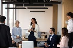 Serious asian coach speaking at diverse corporate group meeting. Serious young female asian coach mentor team leader speaking at diverse corporate group meeting stock photo