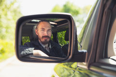 Serious Asian man as a driver looks in car mirror Stock Images