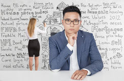 Serious Asian man, blonde woman, home sale Stock Photography