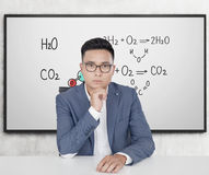 Serious Asian man and chemistry formulas Royalty Free Stock Image