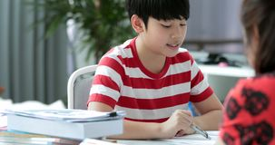 Serious Asian mother with son doing homework in the living room. Mom teaches son how to genius stock footage