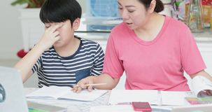 Serious Asian mother with son doing homework in the living room. Mom teaches son how to genius stock video