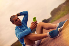 Serious athlete looks at smartphone after training and studying. Lens flare effect Stock Photography