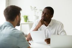 Serious attentive african hr listening to candidate at job inter. Serious attentive african hr manager listening to caucasian candidate at job interview, focused royalty free stock image