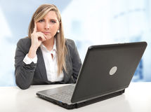 Serious attentive business woman. Serious business woman sitting at her desk with an attentive listener expression Stock Photo