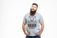 Serious attractive bearded man standing with hands in pockets Royalty Free Stock Photos