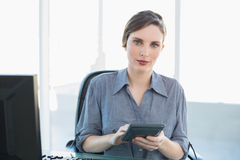 Serious attractive businesswoman holding a calculator sitting at her desk Royalty Free Stock Photo