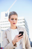 Serious attractive businesswoman sending a text message Stock Photography