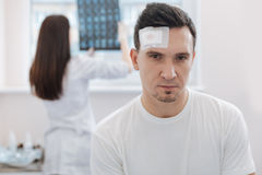 Serious attractive man looking at you. Brain concussion. Serious attractive young men standing in the hospital and looking at you while being wounded Royalty Free Stock Photos