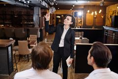 Professional restaurateur examining cleanliness of wineglass. Serious attractive professional restaurateur in stripped suit standing in front of waiting staff stock photography