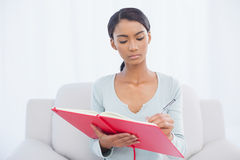 Serious attractive woman sitting on cosy sofa writing Royalty Free Stock Photography