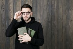 Serious attractive young man with a small beard wearing glasses. And wearing black clothes with books in his hand looks closely at the camera, holding his Royalty Free Stock Photos