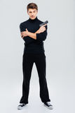 Serious attractive young man standing and holding gun Stock Photos