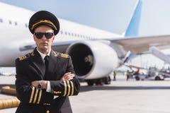 Serious aviator locating near plane Royalty Free Stock Photos