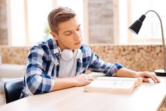Serious avid reader reading a book. Favourite activity. Handsome serious fair-haired teenager having headphones on his neck and reading a book while sitting at Stock Photos