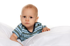 Serious baby boy in the bed Royalty Free Stock Photos