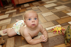 Serious baby boy crawling on the floor Stock Photo