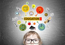 Serious baby boy, education icons. Serious little boy wearing glasses is standing near a blackboard with a colorful study sketch drawn on it Royalty Free Stock Photos