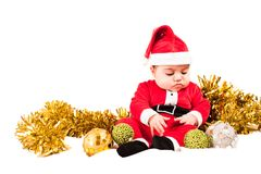 Serious baby dress as santa looking at baubles Royalty Free Stock Image