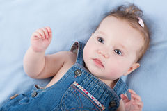 Serious baby girl in a jeans dress Royalty Free Stock Photography