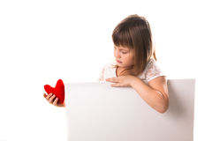 Serious baby girl with red heart in hand, a place inscription Royalty Free Stock Photo
