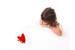 Serious baby girl with red heart in hand, a place inscription Royalty Free Stock Photography
