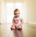Serious baby girl sitting on the floor Royalty Free Stock Images