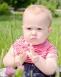 Serious baby girl. Small serious baby girl sitting on the grass in a field in a striped dress stock photography
