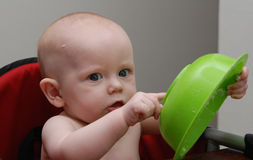 Serious Baby Points at Bowl. A baby looks at the viewer with an expression of shock and surprise as she points at the bottom of a green cereal bowl Stock Photos