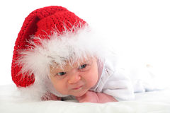 Serious baby in red Christmas hat Stock Image