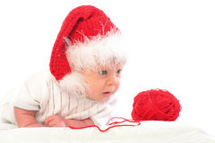 Serious baby in red Christmas hat with a red clew Royalty Free Stock Photography