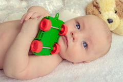 Serious baby with a toy car Royalty Free Stock Photos