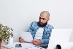 A serious bald businessman with thick black beard and mustache wearing jean shirt being busy with documents. A young frilancer wor Stock Photo