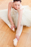 Serious ballet dancer stretching on the floor Stock Photography